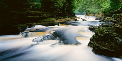 "The last 2 miles of the Presque Isle River is probably my favorite stretch of any river to photograph. With in a couple miles, there are numerous sections of falls and rapids that are accessible from trails on both sides of the river. This photograph is of the last set of falls just before the Presqe Isle River dumps into Lake Superior. When the river runs low, this particular section reveals a unique area of smooth, round ""potholes"" in the riverbed that was created by over thousands of years of constant swirling water.  This section of river is located on the west side of the state in the Porcupine Mountains Wilderness State Park right at the end of County Rd 519 (Thomaston Rd) about 20-25 minutes north of Wakefield.  *For information on purchasing prints and canvas gallery wraps, click the ""Purchasing"" tab at the top of the page. If viewing on your mobile device, scroll to the bottom of the page and click the ""Full Site"" tab to view as if you were on your home PC and then go to the ""Purchase"" tab to for purchasing info. In mobile mode, you will not see the standard navigation bar with the ""Purchase"" tab."