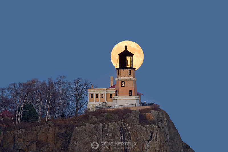 Harvest moon rising behind Split Rock lighthouse