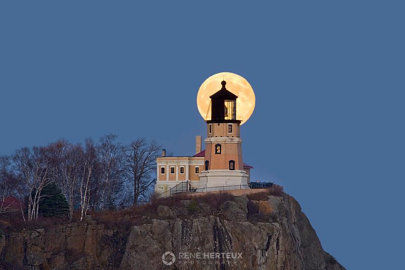 Harvest moon rising behind Split Rock lighthouse