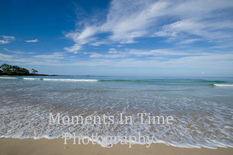 waves and gentle surf, blue sky, some land