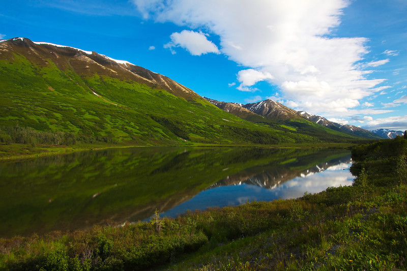 An alpine lake reflects the Kenai Mountains just off of the Seward Highway, a few miles north of Seward, Alaska.