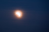 The clouds cause the moon to glow yellow with a fringe of orange.