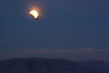 The Earth's penumbra, the refracting sunlight, and the clouds over Mission Peak cause the moon to turn yellow and orange.
