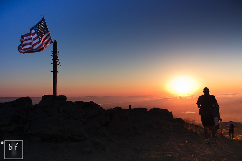 Hikers walk by the American flag on their descent from the summit.