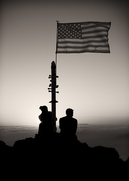 A couple enjoys the view from Mission Peak under the American flag.