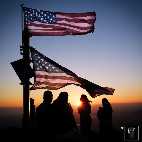 Hikers are greeted by two American flags at the summit.