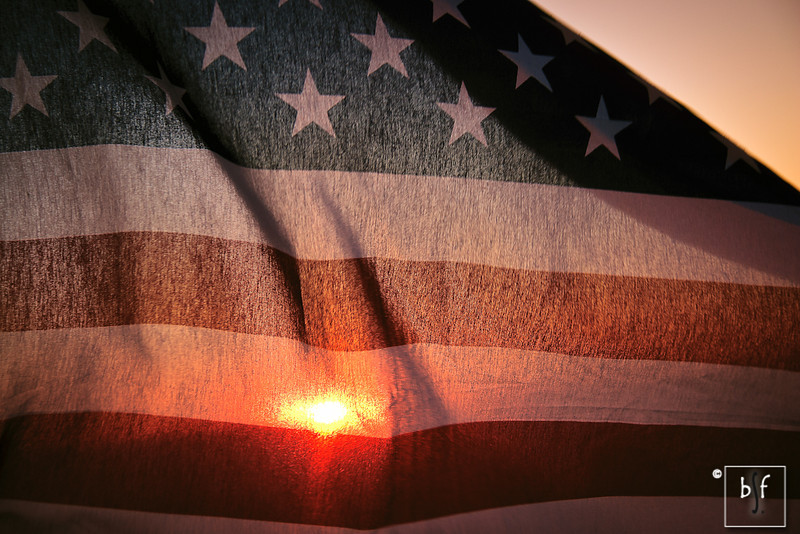 The American flag backlit by the sun.