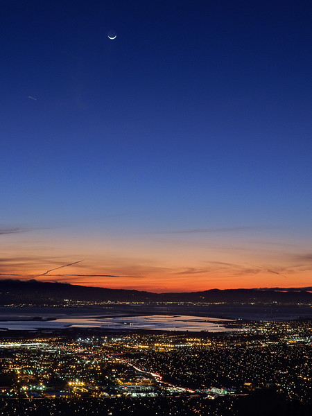 A waxing crescent moon sets on the horizon.