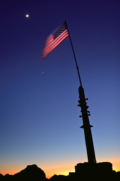 A full view of the waxing crescent moon rising over the American flag.