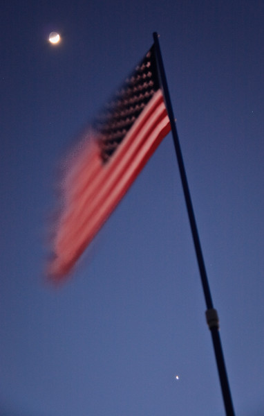 A waxing crescent moon rises over the American flag.