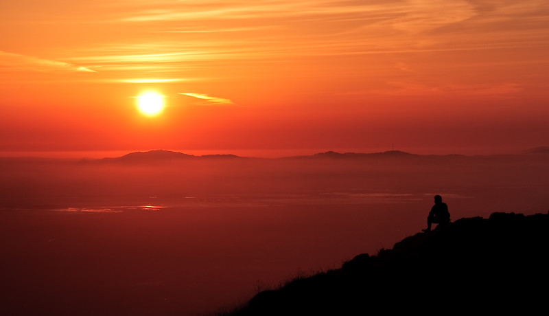A hiker contemplates life as he watches the setting sun.
