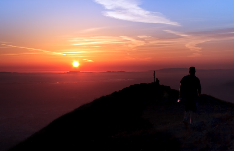 A hiker walks into the sunset at Mission Peak.