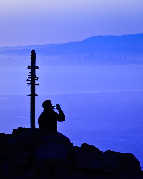 A drink of water at Mission Peak's summit. The San Francisco skyline is in the background.