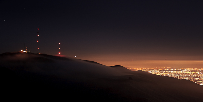 After sunset, the peak became immersed in fog. This 10-second exposure gives the effect of the fog rolling over the hillside. The two radio towers are located on Mt. Allison, which is part of the ridge that includes Mission Peak and Monument Peak.
