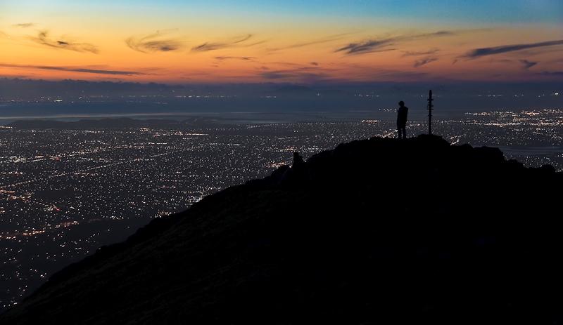 The sun set just below the horizon as the hiker surveys the view.