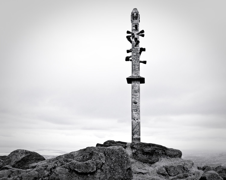The pole marking Mission Peak's summit under overcast skies.