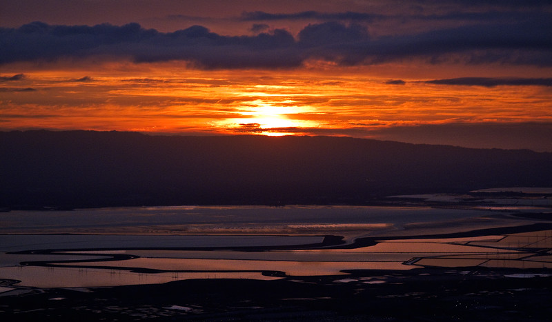 The sun is just about to dip below the horizon. You can see reflections of the cloud cover in the Bay's salt ponds.