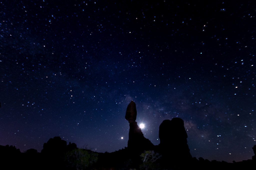 The Milky Way and Balanced Rock in Arches National Park. The moon is just to the right of the Balanced Rock, and the planet Venus is rising on the left of it.