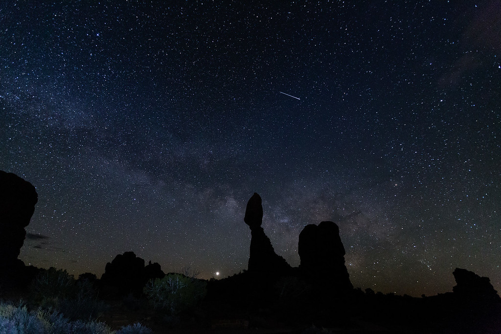 The Milky Way and Balanced Rock in Arches National Park. (The planet Venus is rising just to the left of Balanced Rock.)<br /> Note the satellite passing through the image. (Its trail is constant.)
