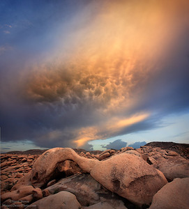 Wild sky with mammatus clouds forming over natural arch in Joshua Tree National Park, California.