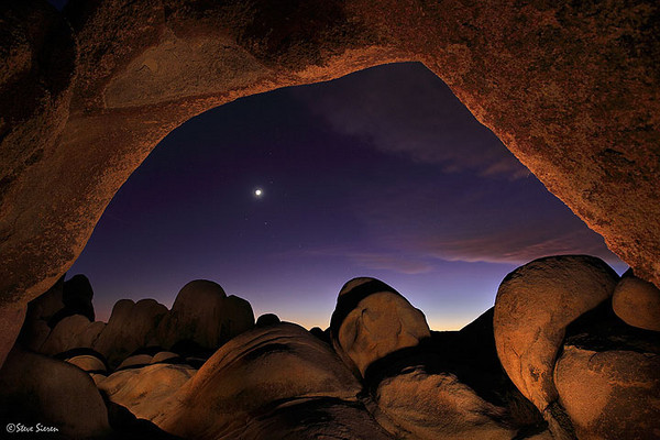 The Other Side  Learn to see in a different way www.ScenicPhotoWorkshops.com  Here is a view looking west from right under the arch in Joshua Tree.  It resembles something out of a Sci flick if you ask me.   I was going to light paint all night long here but decided to leave after my first couple of shot here that evening.  I think I spent more time driving here then visiting the place.   Should of stayed since it was so warm in November.  The moon here is overexposed, I like shooting a scene with out the need to follow rules that other photographer think I should follow.  The wide angle lens rendered the moon a lot smaller then it was and I was perfectly okay with that.