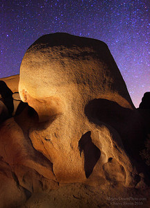 Skull rock painted with light under a night sky at Joshua Tree National Park, Southern California