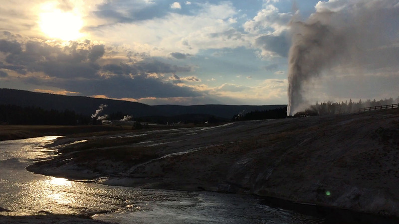 The Firehole geyser basin and the Beehive geyser at sunset