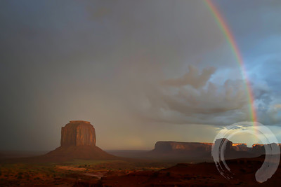 "Rainbow over Monument Valley  After the sun had gone below the horizon, we were treated to this huge rainbow.  I rushed down to the firs switchback & grabbed my pocket camera to catch it, knowing that by the time I got my ""big"" camera out & set up, it would probably be gone."