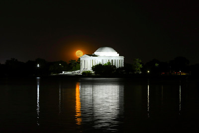 The rising moon seems to balance on the roof's edge of the Jefferson Memorial.