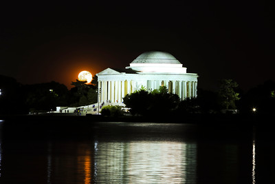 The full moon peeks through next to the Thomas Jefferson Memorial