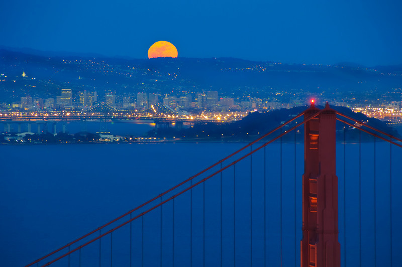 """Full Moon over Golden Gate. Taken from the Marin Headlands at dusk, I calculated exactly where the moon was going to be rising and made sure I was camped out to watch.  It popped-up right at dusk with the royal blue skies!   With a little bit of the Golden Gate bridge lit up, it makes QUITE the perfect moon picture!   More moons can be seen in my Moon Gallery with Moonrises, Moonsets and funny placements with the moon!   DSC0939  <a href=""""http://www.jharrisonphoto.com/Landscapes/Moonscapes-Moonrises-Moonsets/4697829_YaGjF"""">http://www.jharrisonphoto.com/Landscapes/Moonscapes-Moonrises-Moonsets/4697829_YaGjF</a>"""