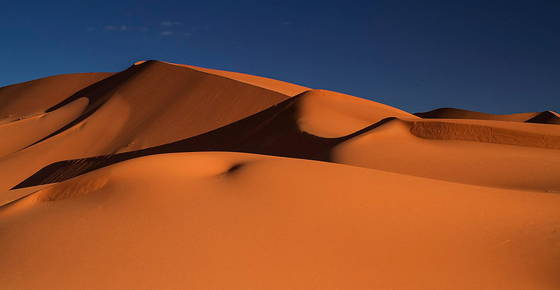 The red orange coloured sand of Erg Chebbi with a clear blue sky.