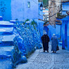 Two Moroccan women walking down the street of Chefchaouen.