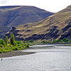A steelhead fly fishing angler on the Snake River is dwarfed by his surroundings.