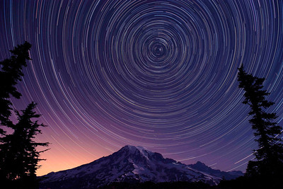 """Perseids"" Shot on August 11, 2012 during the height of the Perseid meteor showers looking north at the south face of Mt. Rainier. This approximately 31/2 hour exposure clearly shows at least 3 meteor traces: 2 right above the mountain and another next to the tree on the right. The North Star is the bright one in the center and the other stars are part of the Little and Big Dippers. Note the trail of light on the right shoulder of the mountain, showing the lamps of hikers attempting to summit that morning and who have left Camp Muir at about 2 am. The incredible resolution of the Nikon D3X clearly shows the different colors of the star trails, indicating the relative temperatures of their nuclear fires: white being the hottest, blue and pink cooler."