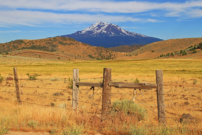 A weathered fence line contrasts against the rolling hills framing Mt. Shasta near Weed, CA