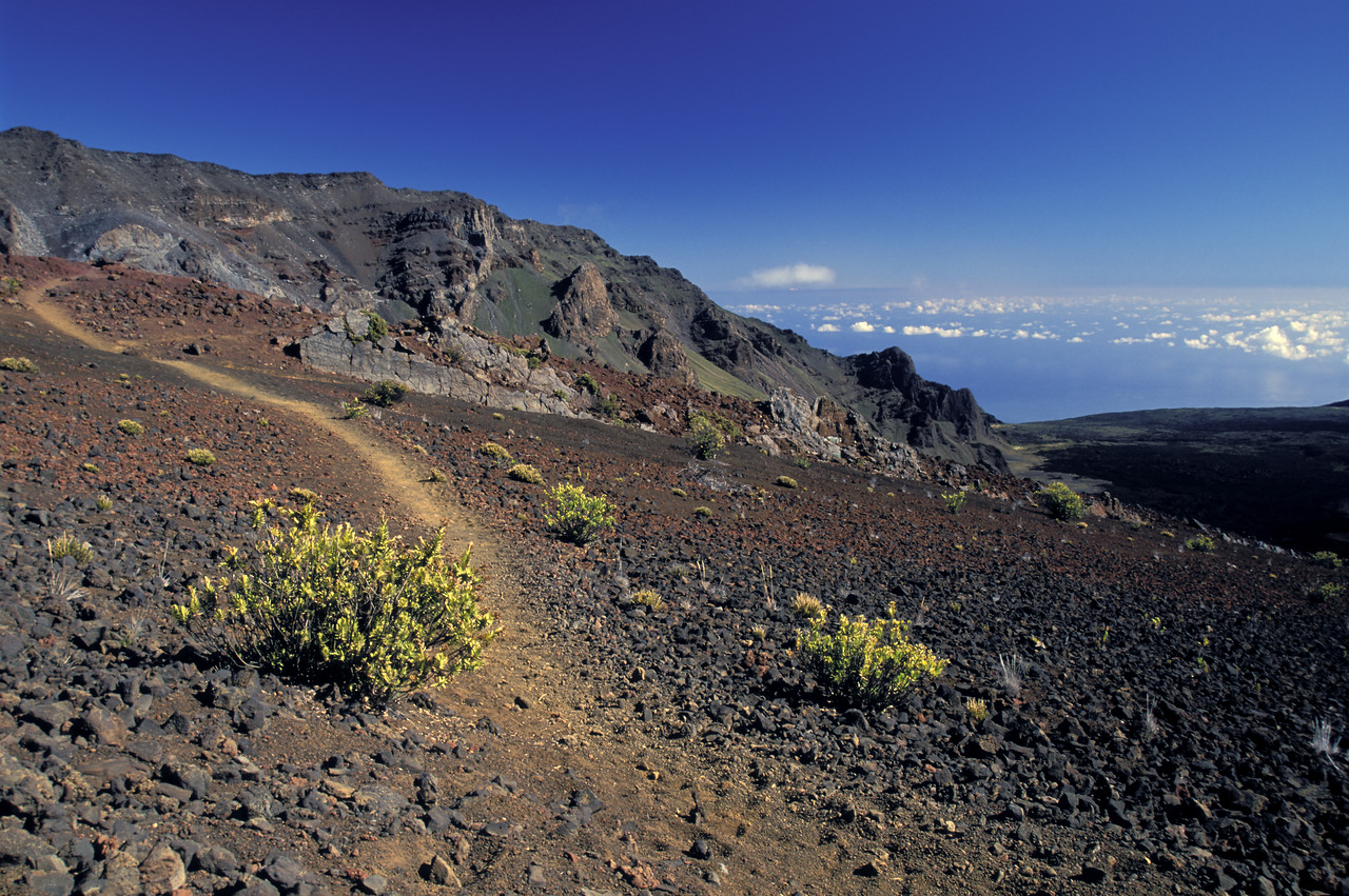 A trail winds down the caldera of Haleakala volcano on the island of Maui, Hawaii