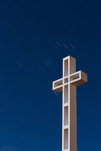 Mt Soledad cross illuminated by the full moon and the Little Dipper making star trails in the background.
