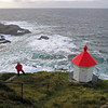 FACING THE OCEAN<br /> The lighthouse at the exposed north side of Nyksund Island has experienced a stormy day or two. Bur it sits safely at its rocy shelf, well elevated above the ocean and the seaspray. Here – a day in September, with salty spray like a hazy mist on the horizon.