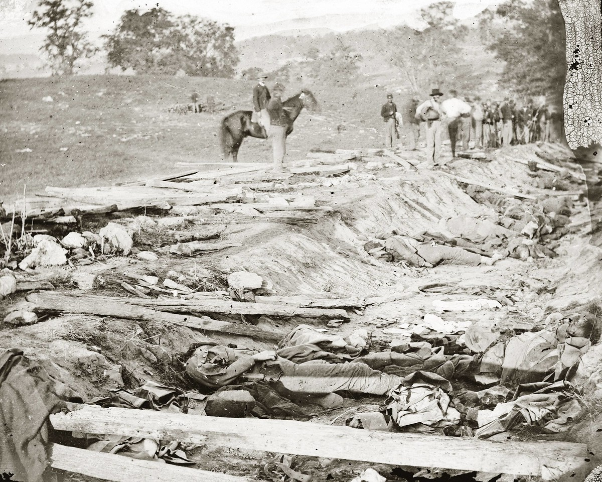 Alexander Gardner's Famous image of Sunken Road or Bloody Lane taken days after the battle, September 19, 1862.  I visited this site for the first time August 23, 2009 and as a photographer myself I became highly interested where Gardner stood to gather these images.  Antietam guide, William Sagle, took us through the battlefield and showed me this image for the first time.  Standing at the Roulette Farm Lane intersection with Sunken Road.  I could not visualize an interaction between this image and the existing terrain.  Something just wasn't right.  I thought perhaps the image was printed backwards.  It would make more sense with hill contour and what appeared to be an upwards slope to the lane....  After I got home I analyzed the print in detail.  The buttons on the the dead mans jacket are on his right meaning the print is correctly printed.  So I got hooked on the problem and began further analysis.  <br /> <br /> Notice the shadow caused by the wood fence rail in the foreground and the shadows caused by the vertical twigs and the man standing by the ditch.  I will try to duplicate these shadows at home on the same day and month of Gardners image to determine sun angles so I can better locate this spot.  It is difficult to estimate the height of the rail and the distance of the body from the rail.   I estimate the middle height of the 4 inch rail is 16 inches off the ground and the middle height of the shadow on the leg is 7 inches of the ground.  I also estimate the horizontal middle of the rail is about 4 feet from the body.<br /> <br /> I believe this image was taken somewhere along the inclined area of Bloody lane. <br /> <br />  See next image.