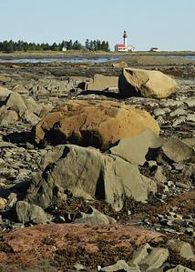 Métis-sur-mer, Qc, Canada: phare à marée basse, différentes couleur de roches présente sur la côte sud de la Gaspésie / Lighthouse at low tide. We can observe various colors of rocks that are present along the Gaspe shores.