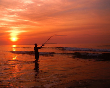 A fisherman surf casts at sunrise, Old Orchard Beach Maine.
