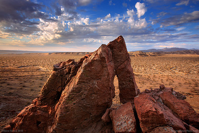 A small arch in Red Rock Canyon State Park, California.  This small overlooks the Mojave Desert from the cliffs above the desert floor.  A clearing storm brings soft light to the El Paso Mountain Range in the background.