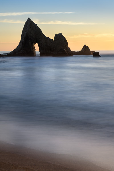 Sunset at Martin's Beach in Northern California. Silky blue water feels peaceful against a bright organe sunset.