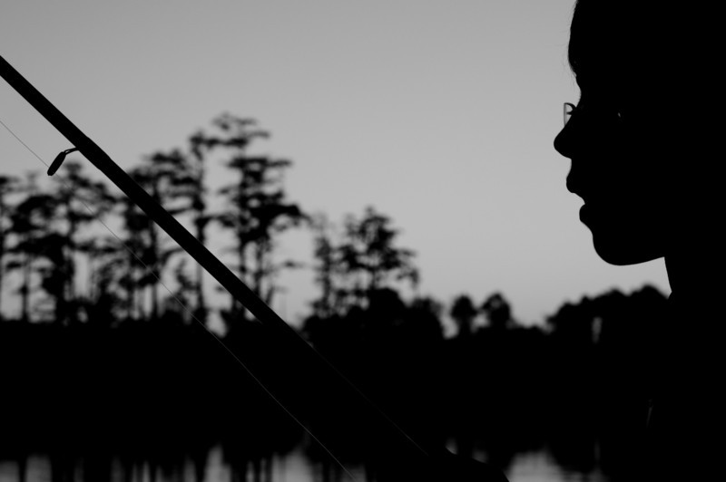Silhouette of boy fishing at Rhodes Pond NC Wildlife Resource Commission