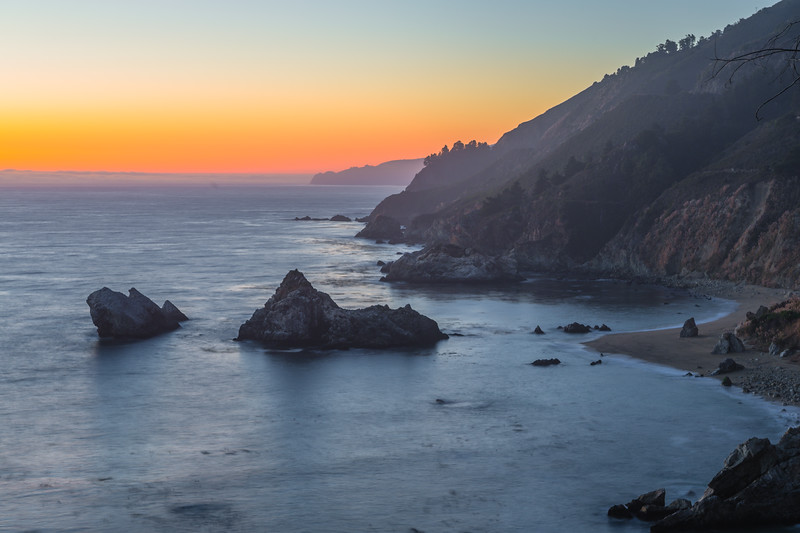 """""""Big Sur Sunset"""" Just a simple coastline shot at sunset along the Northern California Coastline near Big Sur and Julia Pfeiffer Burns State Park near McWay Falls. A simple orange glow with fog in the distance. The steep cliffs drop down quickly to the ragged coastline with a few sea stacks below. It would be fun to be out there in a kayak at sunset instead of up on the hills! Yet another place I want to park my chair on a Friday afternoon!!! — in Big Sur, CA."""