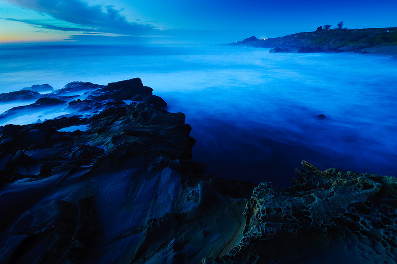 """Edge of the World""   Northern California Coastline at Dusk.  The waves smooth and ethereal, the rocks looking like they were from another planet.  This is a long exposure at dusk that I shot last night.  I love the blue tones that come out at dusk and the smooth waves from the long exposure.  The rocks with the craters/crevices really helped give it that unusual look and had me thinking of the title - if there were an edge of the world, this is what it would look like!"