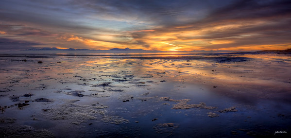 Salty Mud Flats comprise a vast majority of the shoreline in White Rock Bay on Antelope Island State Park in Salt Lake, Utah. I had to be very careful where I stepped, not wanting to get my boots too muddy.  My origianal compositional idea was to have a certain rock formation in the foreground for this panorama, but as the sun set I noticed that the muddy flats were a beautiful and unique reflective foreground in themselves.    I loved this evening's sunset/moonrise. The mountains in the distance, covered in a beautiful fog layer to the south, and the colors of the clouds in the sky reflecting on the shore, and full moon behind me all combine to make magic.  I didn't just observe this sunset, I took part in it.  This is a panoramic image created from 6 vertical HDR frames. Each HDR frame was created from 3 RAW images using Photomatix Pro and Photoshop CS4.