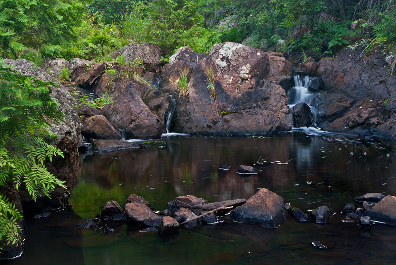 This beautiful little falls flows through a deep pink-tinged rocky ravine and is located in a remote area not far from the town of National Mine Michigan.