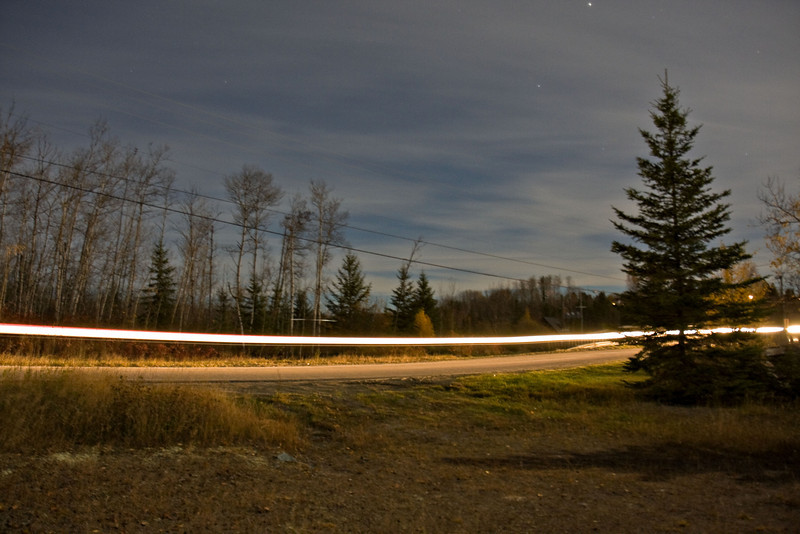 Charlton, Ontario, under a full moon. Vehicle passing by on Highway 573.